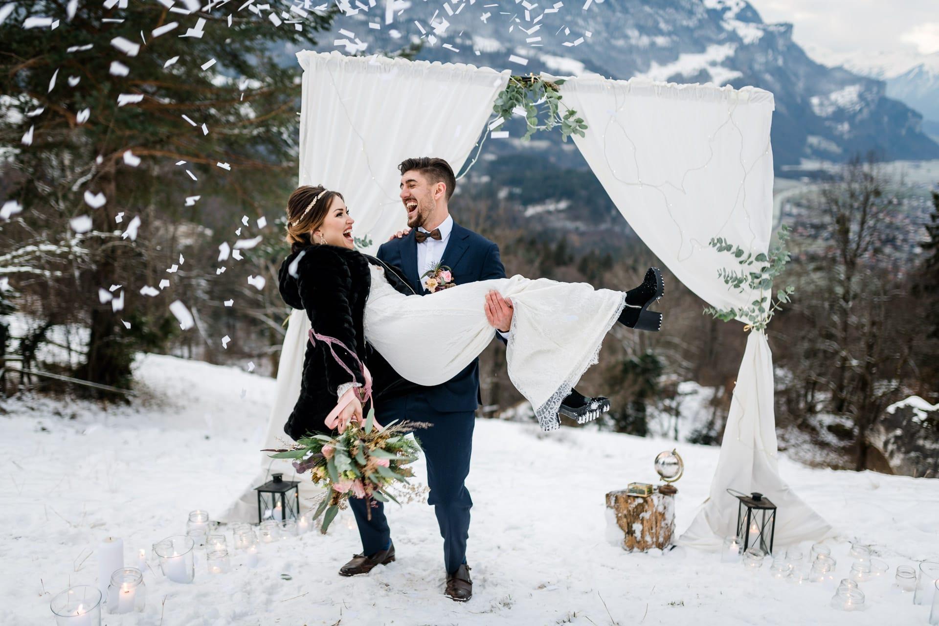 Bräutigam trägt seine Braut auf den Händen nach der Winterhochzeit in den Schweizer Bergen