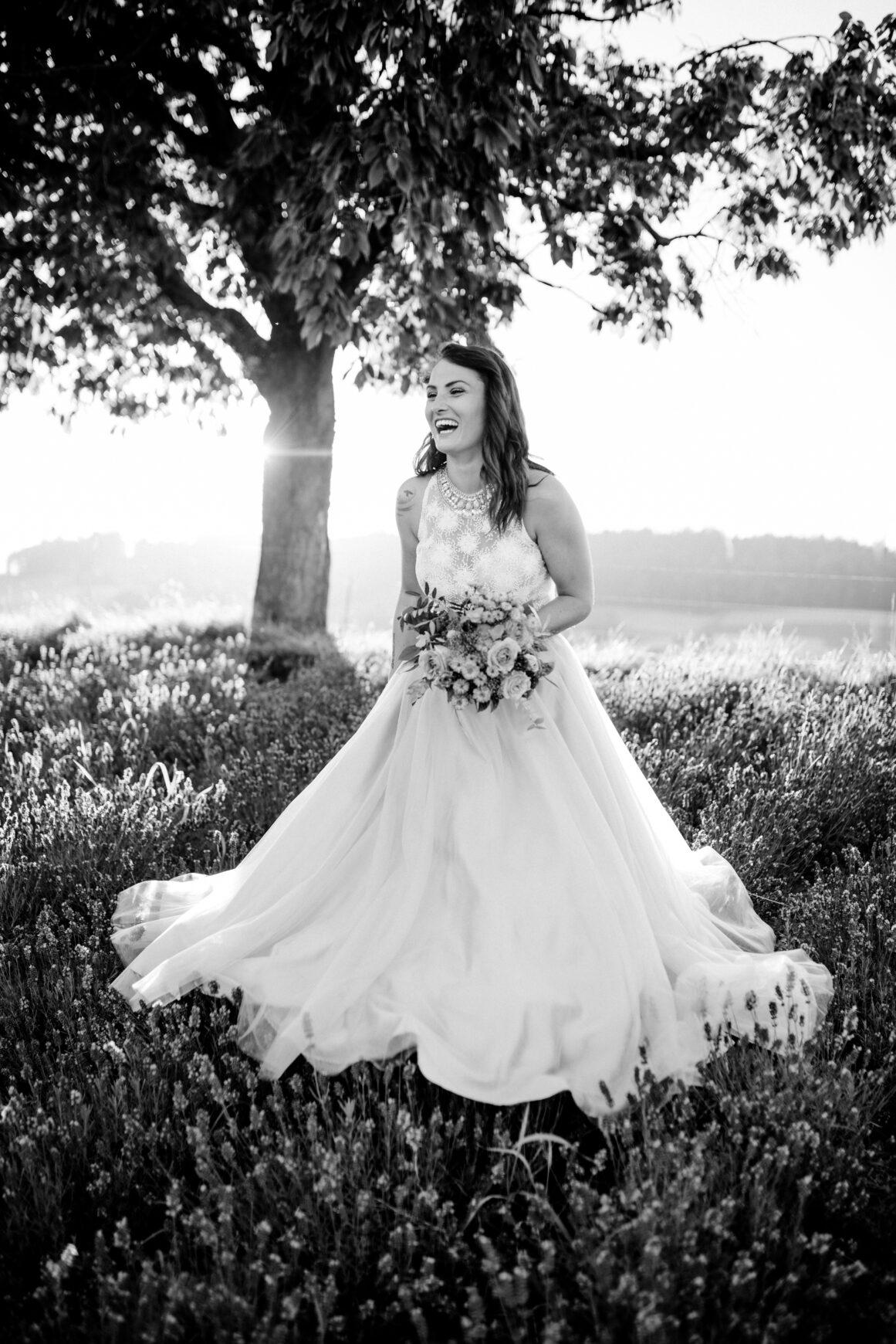 Braut während After-Wedding Shooting im Lavendelfeld mit Hochzeitskleid zum Sonnenuntergang.