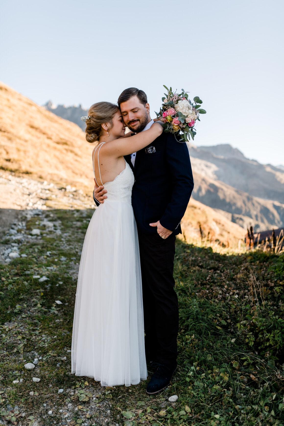 Brautpaar im Hochzeitskleid und Hochzeitsanzug beim Paarshooting bei einer romantischen Berghochzeit auf der Belalp in den Schweizer Bergen