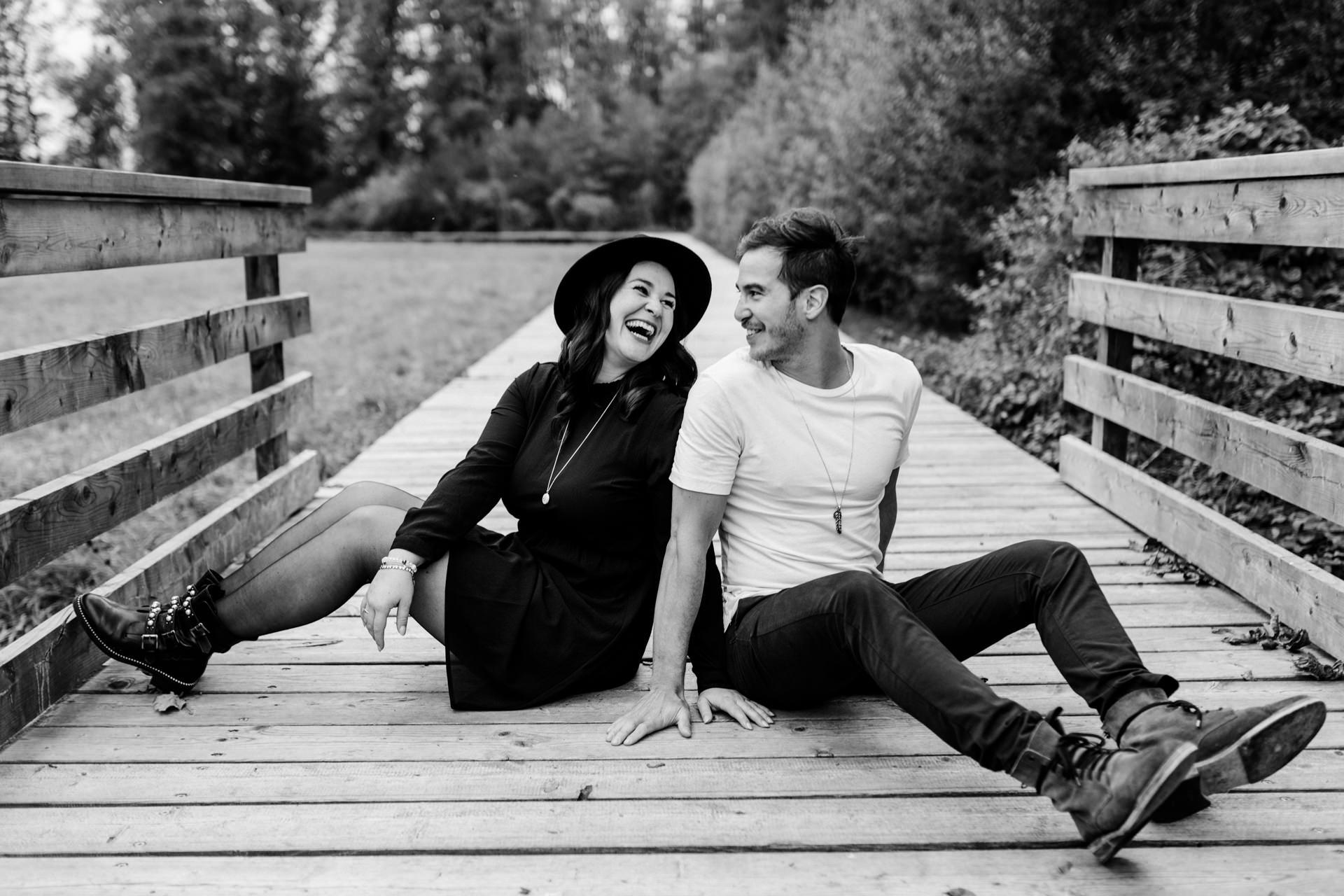 Paar sitzt auf Steg während Paarshooting an einem See in der Schweiz und lacht.