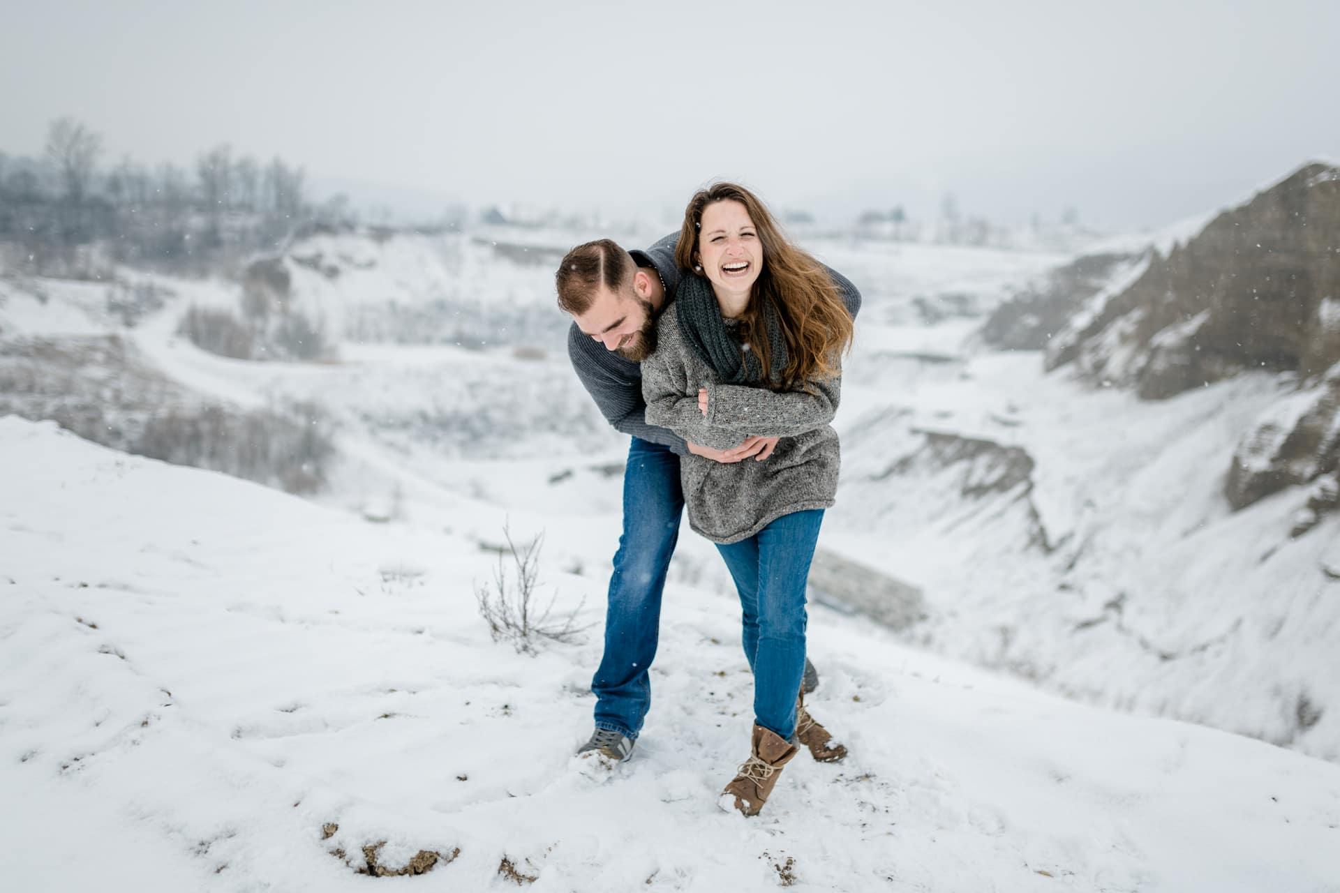 Verliebtes Paar tollt herum während winterlichem Verlobungsshooting im Schnee nahe Solothurn