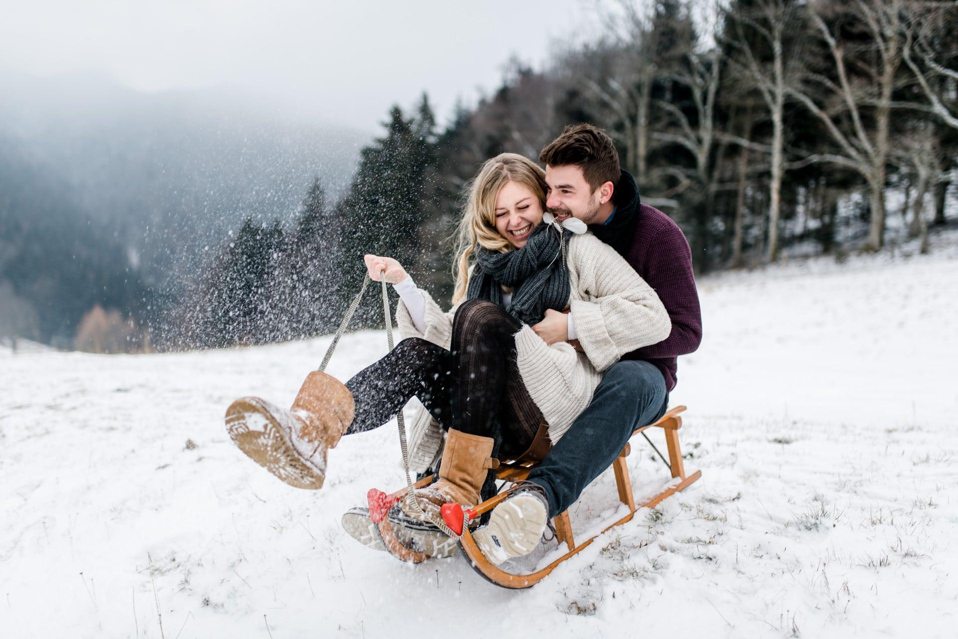 Paar auf dem Schlitten bei einem Paarshooting im Winter in der Schweiz