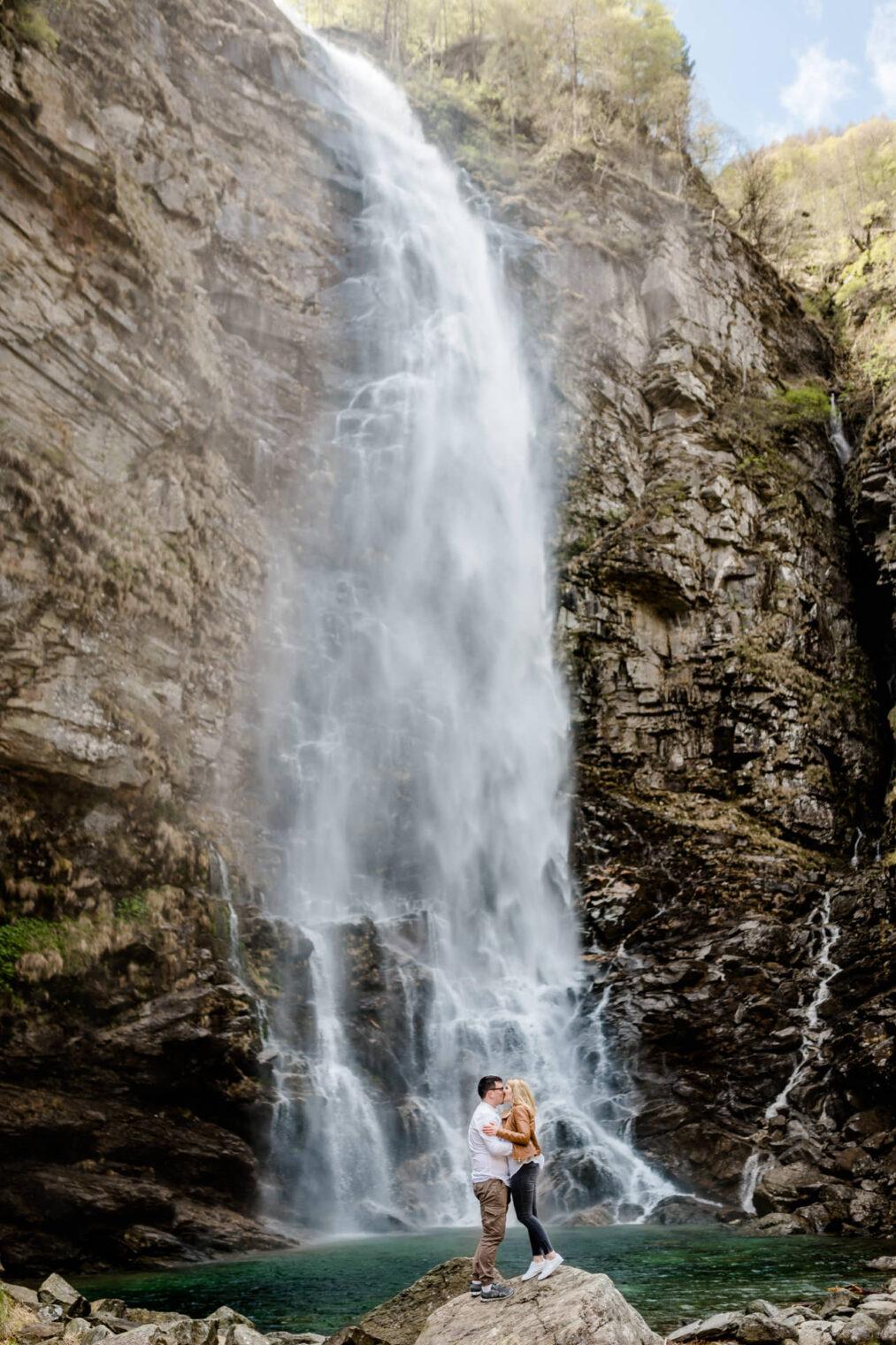 Paar küsst sich vor Wasserfall im Verzasca Tal im Tessin in der Schweiz bei einem Adventure Shooting