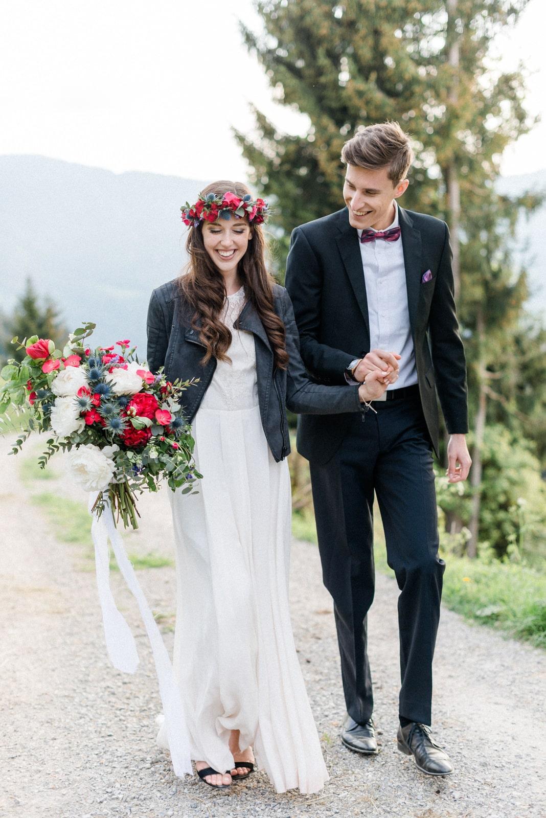Brautpaar läuft mit Hochzeitsstraus und Blumen in den Haaren gemeinsam zur Hochzeitslocation