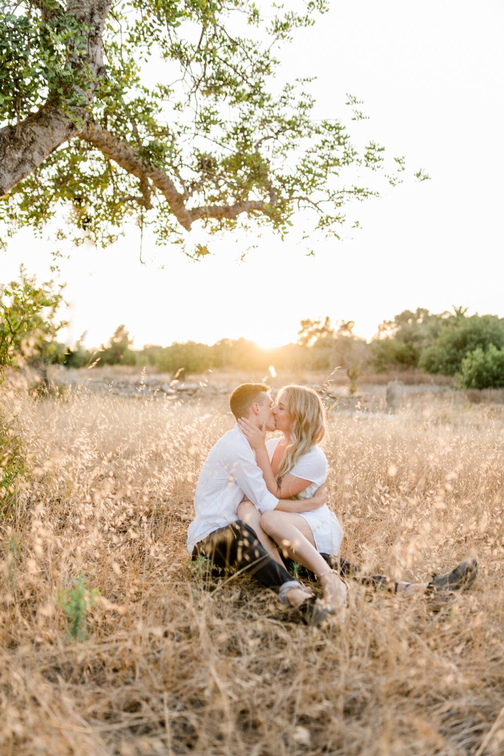 Paar küsst sich während Paarshooting zum Sonnenuntergang auf Ibiza