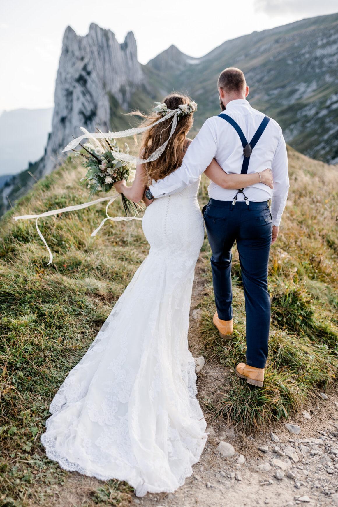Brautpaar im Hochzeitskleid und im Hochzeitsanzug mit Brautstrauss während einem After-Wedding Shooting in den Schweizer Bergen