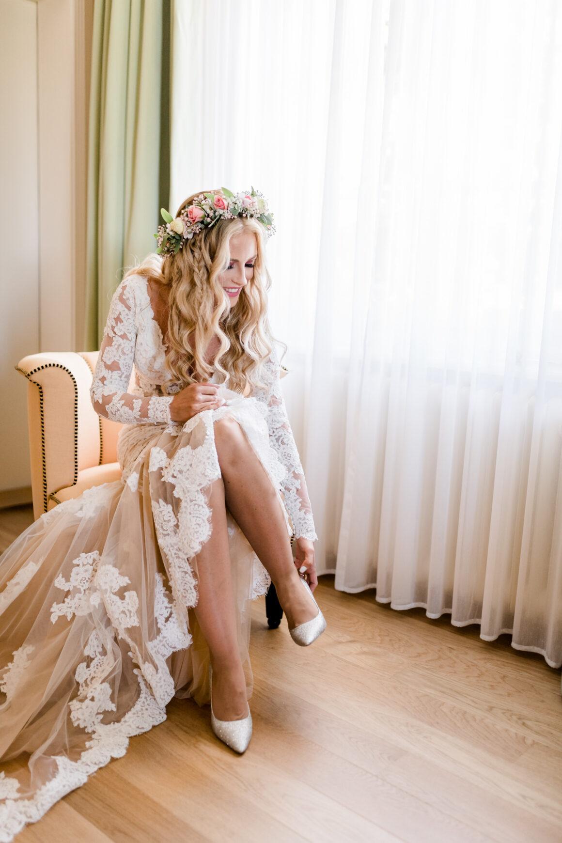 Braut zieht ihre Jimmy Choo Hochzeitsschuhe beim Getting Ready an. Hochzeitsreportagebilder Schweiz