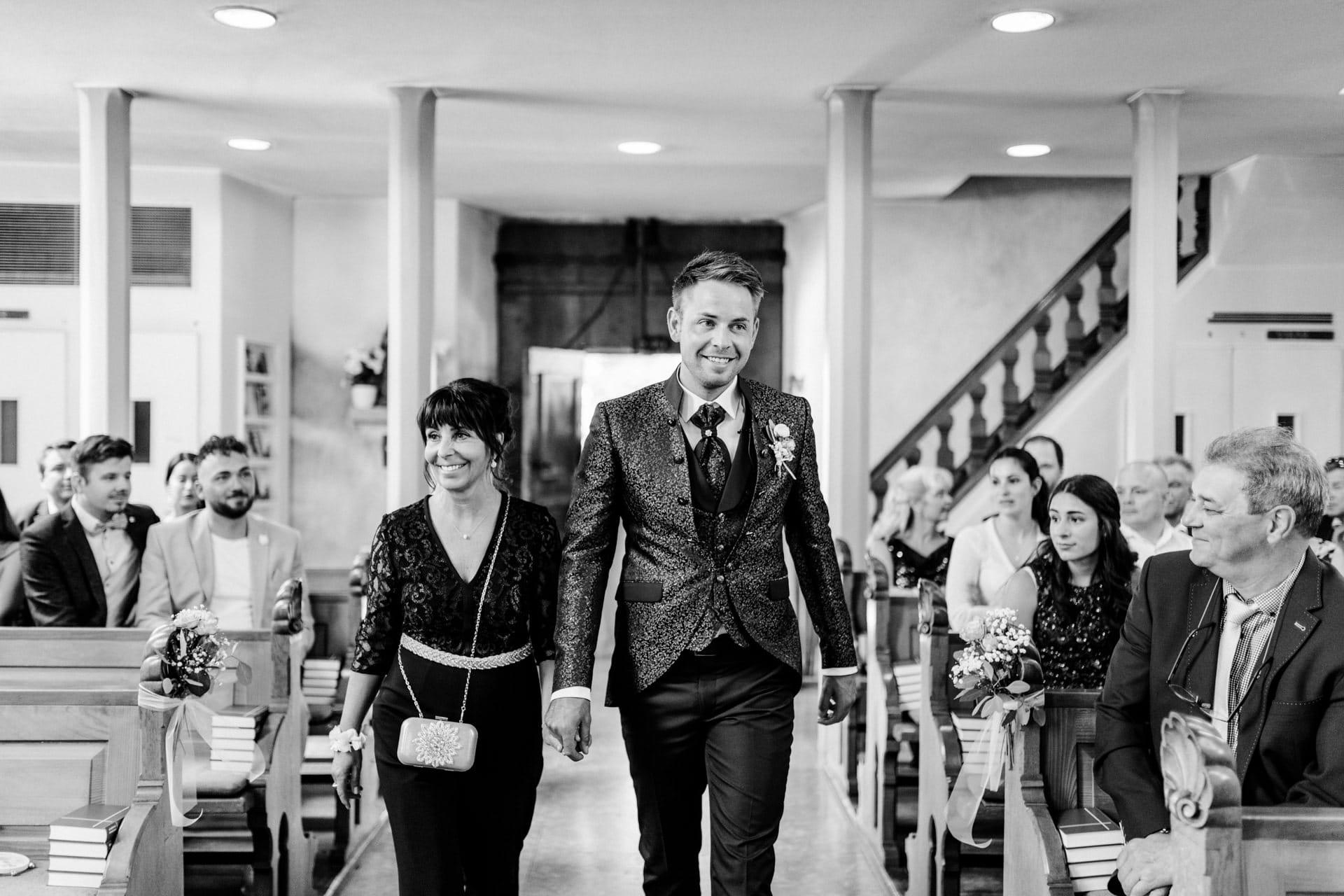 Bräutigam läuft mit Mutter den Mittelgang der Kirche entlang. Hochzeitsreportage Schweiz
