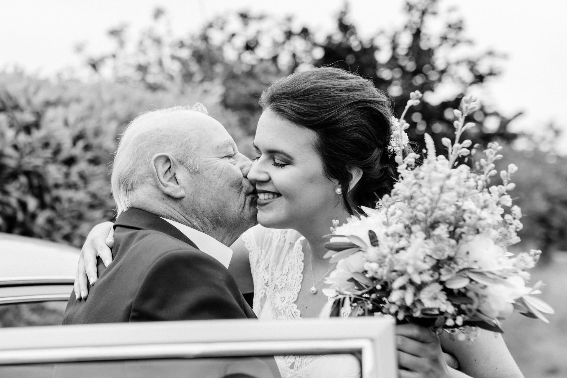 Grossvater küsst Braut auf die Backe nach der Trauung am Hochzeitstag